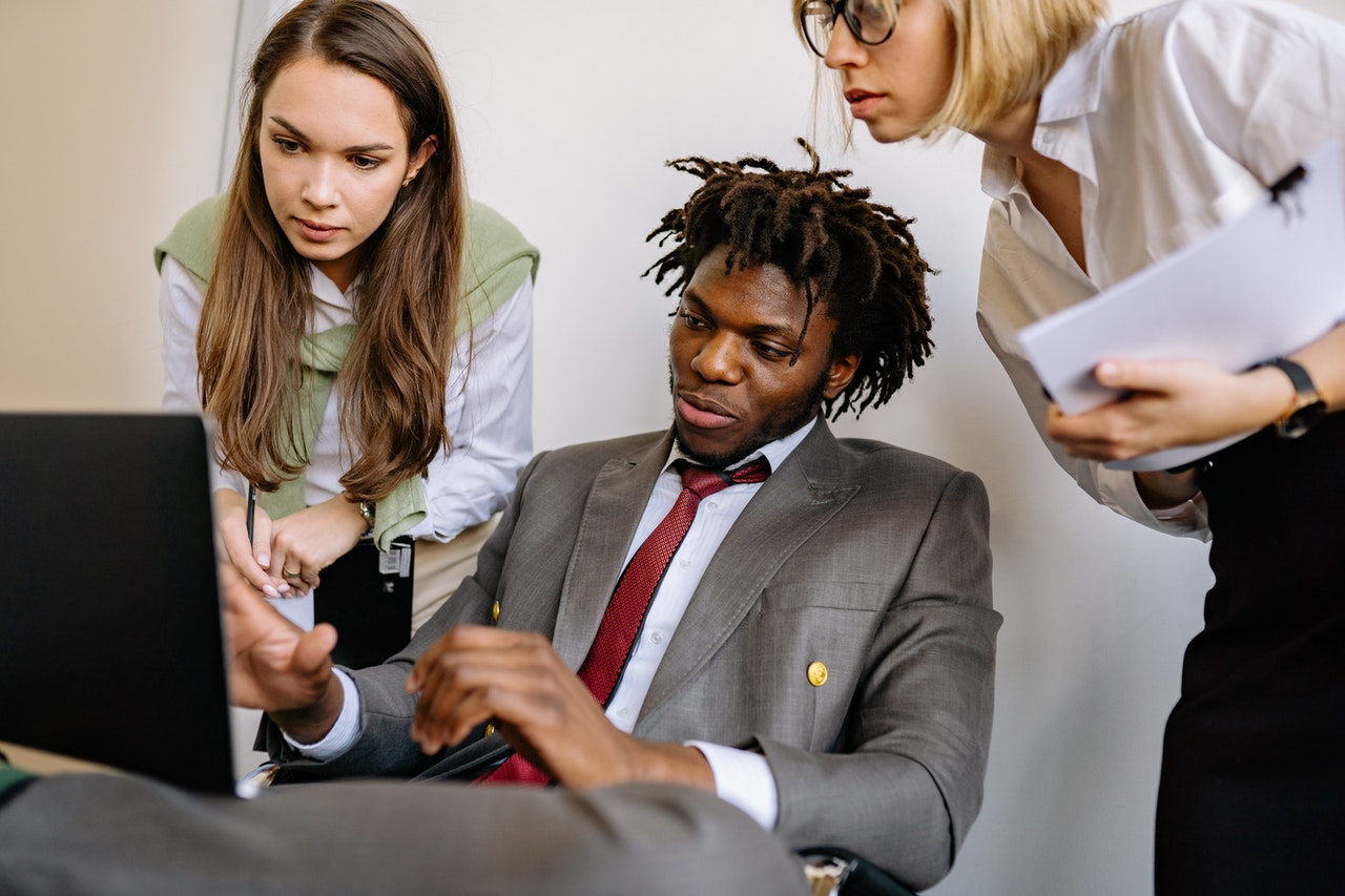 A man explaining CRM basics to his female colleagues